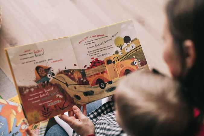 woman reading book to toddler